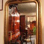 Antieke spiegel in houten vergulde lijst met kuifdecoratie